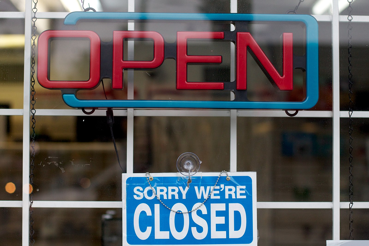 """Store with two signs: 'Open' and 'Sorry we're closed'. Creative Commons photo by """"cogdogblog"""" —Source: https://www.flickr.com/photos/cogdog/7155294657/"""